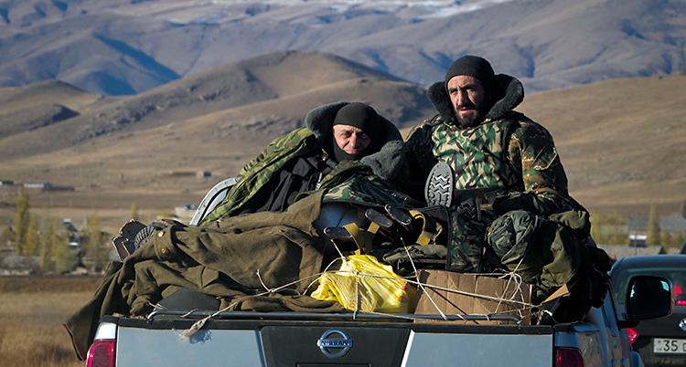Två soldater sitter på flaket till en bil. De har stridskläder på sig. I bakgrunden syns höga berg.