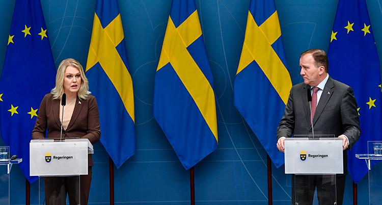 Ministern Lena Hallengren och statsminister Stefan Löfven pratar för journalister. De står på en scen och pratar i varsin mikrofon. I bakgrunden finns svenska flaggor och EUs flagga.
