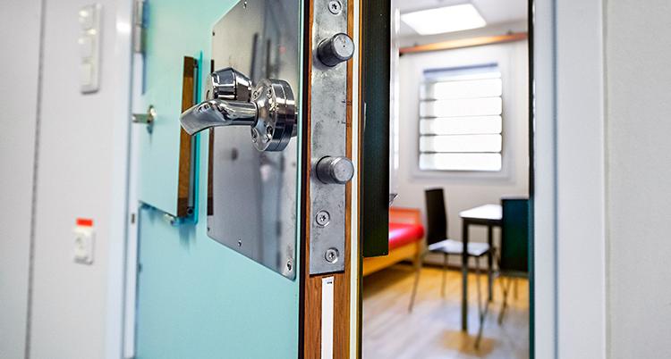 En dörr står på glänt och vi ser lite av en cell på ett häkte. Inne i cellen finns en säng och ett bord med två stolar. Det är galler för fönstret.