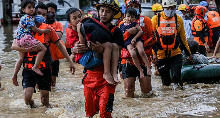 Räddningsarbetare bär barn i sina armar över översvämmat område.