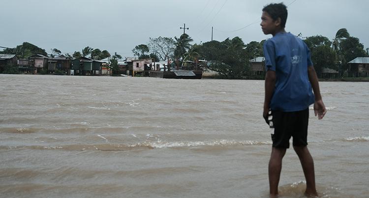 En pojke tittar ut över et översvämmat område.Han står i vatten som går upp till hans vader.
