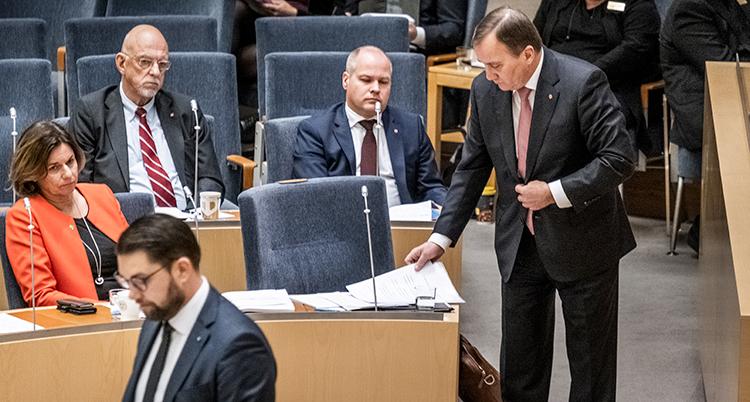 flera politiker i riksdagens lokaler. Statsministern står upp vid sin stol.