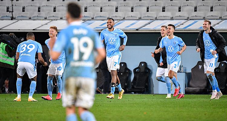 Bilden är från en stadion för fotboll. Spelare i Malmö FF springer på gräset. De är glada. De har ljusblå tröjor.