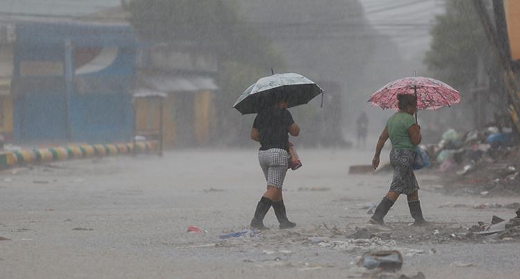 Vi är utomhus i landet Honduras. Bilden visar två kvinnor som går på en gata. De har paraplyer. Det regnar och det är mycket vatten på marken.
