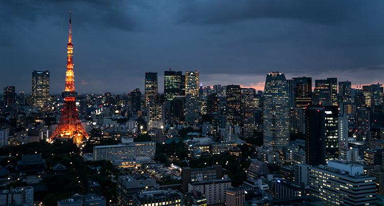 En vy över Tokyo på natten. Skyskrapor och ett vackert byggnadstorn syns. Det lyser i fönstren.