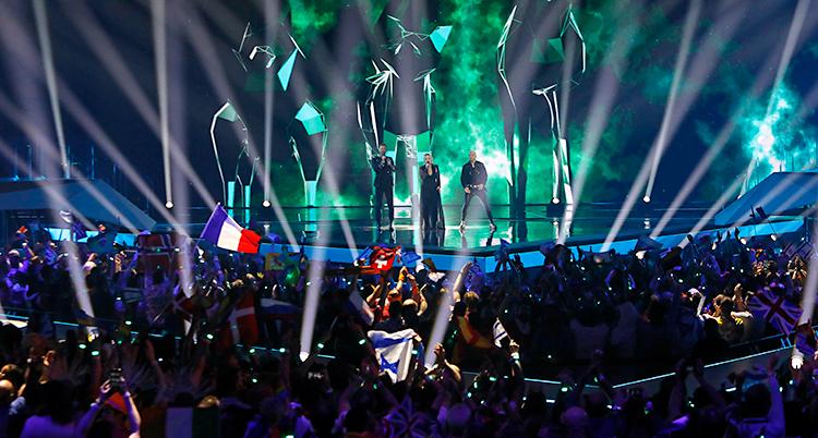 Tre artister står på en scen och sjunger. Framför dem är en stor publik. Några flaggor finns i publiken.