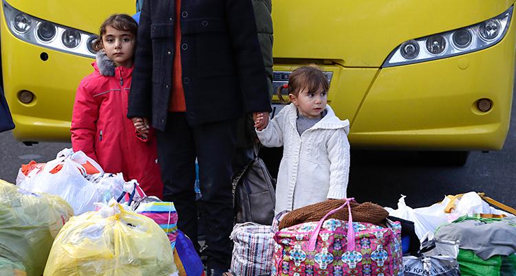 Två små barn står framför en buss. De håller en vuxen i handen. De har massa väskor och påsar.