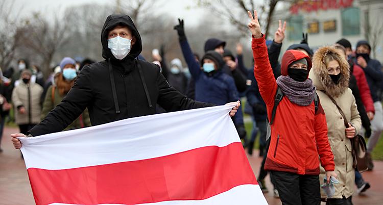 Människor går på gatan. De har munskydd på sig. De gör v-tecken med fingrarna. En av dem har en röd och vit flagga.