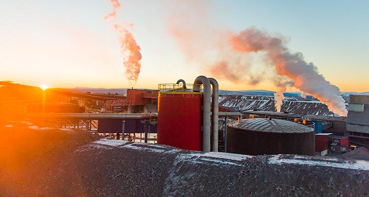 Bilden är tagen utomhus i Kiruna. Vi ser flera stora byggnader. Det kommer rök från några skorstenar.