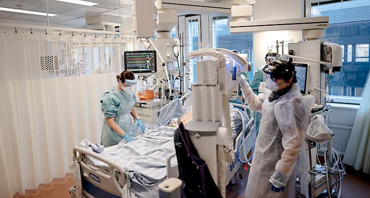 Ett rum på ett sjukhus. Två personer jobbar med skyddskläder och skydd för ansiktet. De står bredvid en sjukhussäng.