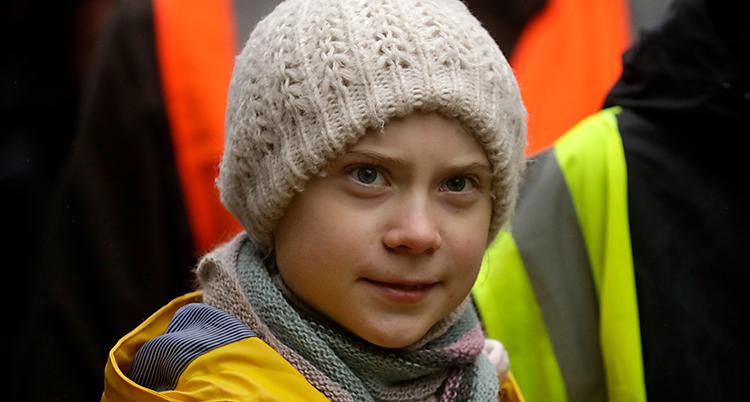Greta Thunberg på en strejk för klimatet. Hon har en vit mössa och en gul regnjacka.