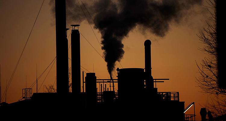 Det är kväll. Vi ser siluetten av en stor fabrik med skorstenar. Det kommer ut rök från fabriken.