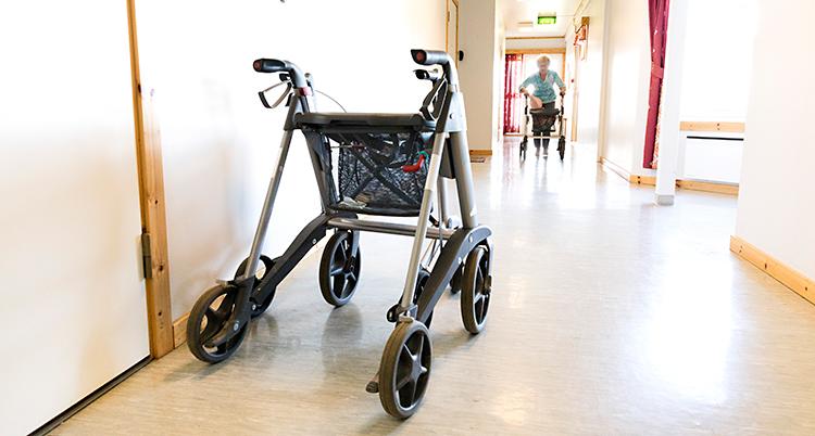 En korridor på ett hem för gamla. Det står en rullator i korridoren. Längre bort går en person med en rullator.
