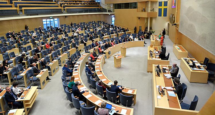 Stolar i riksdagen står i halvmåneformade rader mot ett podium.