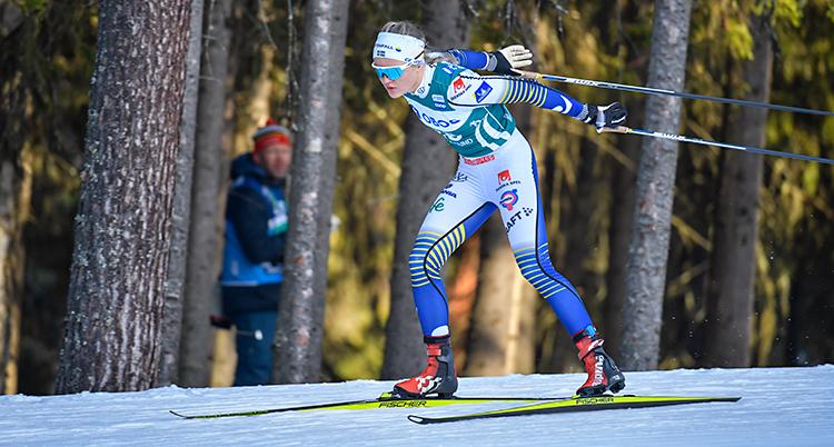 Linn Svahn åker en tävling i längdskidor. Hon åker på en bana av snö. Bakom syns en skog. Hon har en tajt dräkt, mössa och solglasögon.