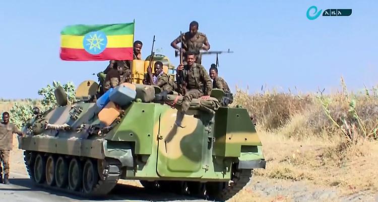 Vi ser en stridsvagn eller en bandvagn på en väg. Vagnen är grön. Det sitter soldater på den. Och en etiopisk flagga.