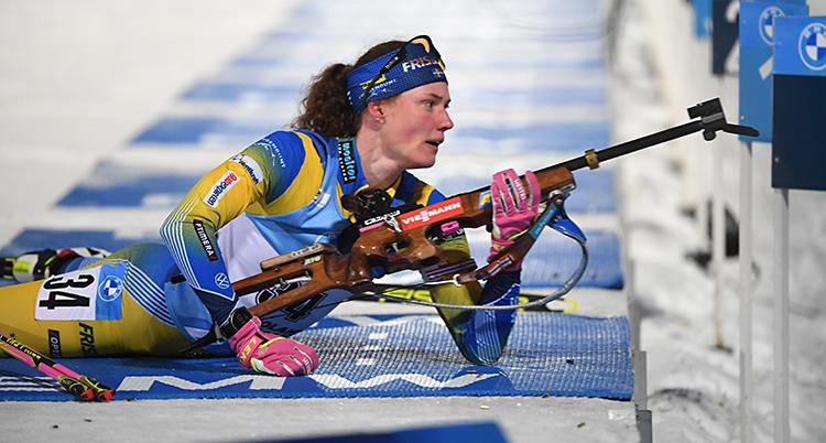 Hanna Öberg lägger sig ned för att skjuta. Hon har fram sitt gevär. Hon har skidor på sig och hon har Sveriges dräkt i gult och blått.