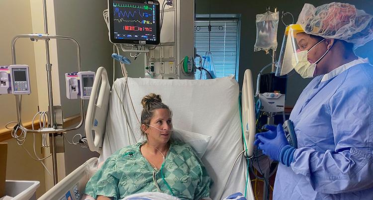 Hon ligger i en sjukhussäng. Hon har en slang i nästan för att få hjälp att andas,