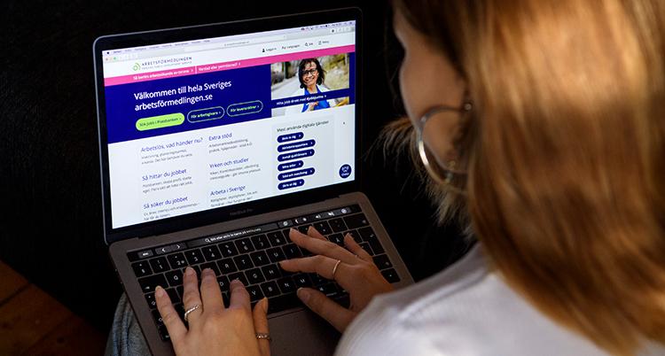 En kvinna har en dator i knät. På skärmen syns att hon besöker Arbetsförmedlingen.