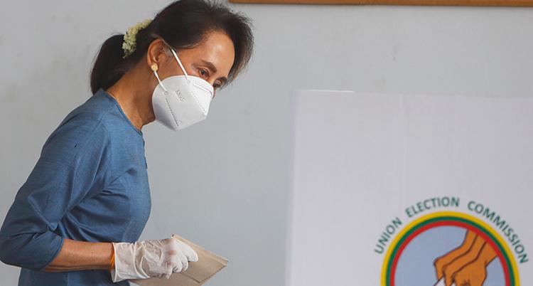 En kvinna med mörkt hår, ljusblå klänning och munskydd håller ett papper i handen, som har en plasthandske.