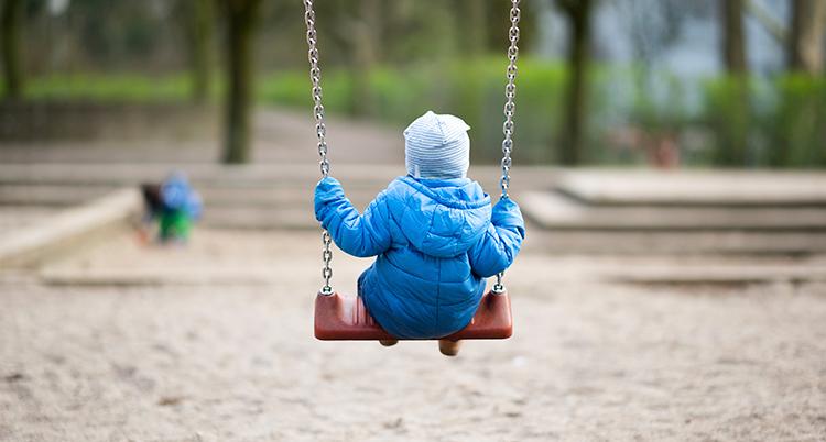 Ett litet barn i blå jacka och mössa sitter på en gunga med ryggen vänd mot kameran