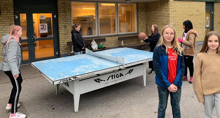 Flera barn spelar boll runt ett pingisbord utomhus. Två tjejer står vända mot kameran framför pingisbordet, den ena har ljus hår och blå jacka, den andra har brunt hår och beige tröja.
