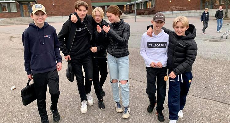 Ett gäng med ungdomar. går över en skolgård. De ser glada ut och håller om varandra.