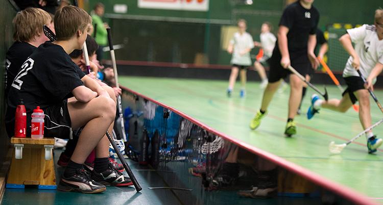 Några pojkar sitter på en bänk bredvid en plan där andra barn spelar innebandy. Pojkarna är avbytare