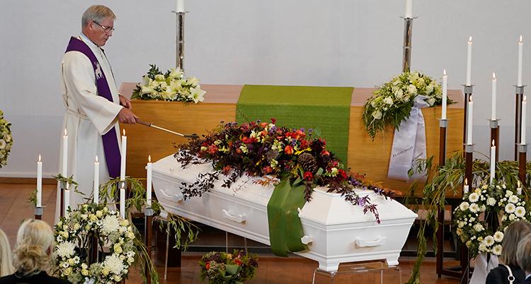 En präst står vid en kista. Kistan har blommor på sig.