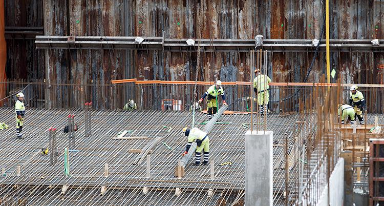 Byggjobbare i hjälmar jobbar på en byggarbetsplats