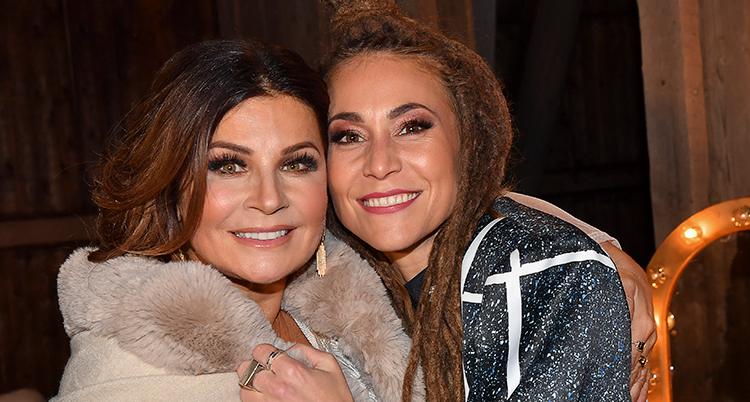 Två kvinnor håller om varandra och har huvudena tätt och tittar in i kameran. Den ena har vit päls och den andra har blågrå kappa.