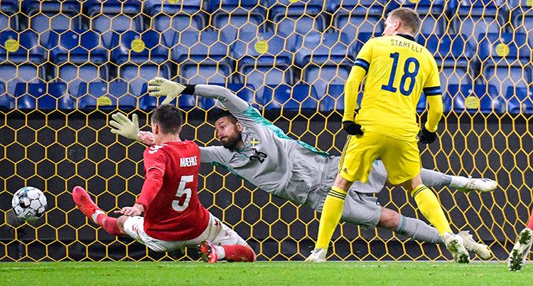 En svensk spelare ser på när en dansk kastar sig fram och skjuter bollen i mål. Svenske målvakten kastar sig raklång men han når inte fram till bollen.
