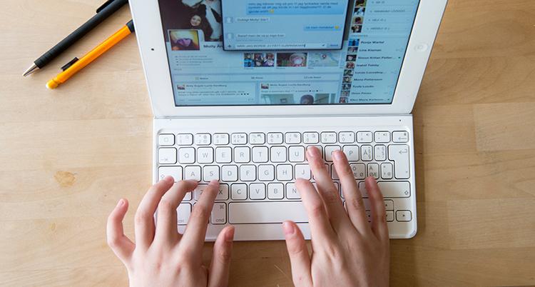 Två händer skriver på ett tangentbord på en dator.