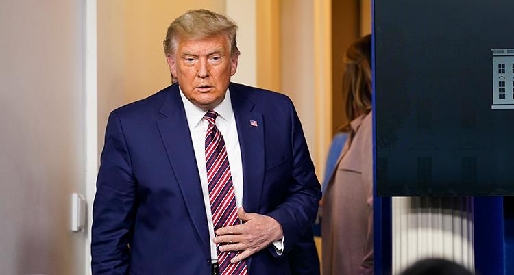 Han har blå kostym och röd slips.