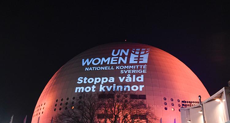 Globen upplyst i orange mot en svart himmel. I vitt lyser texten Stoppa våld mot kvinnor på Globen.