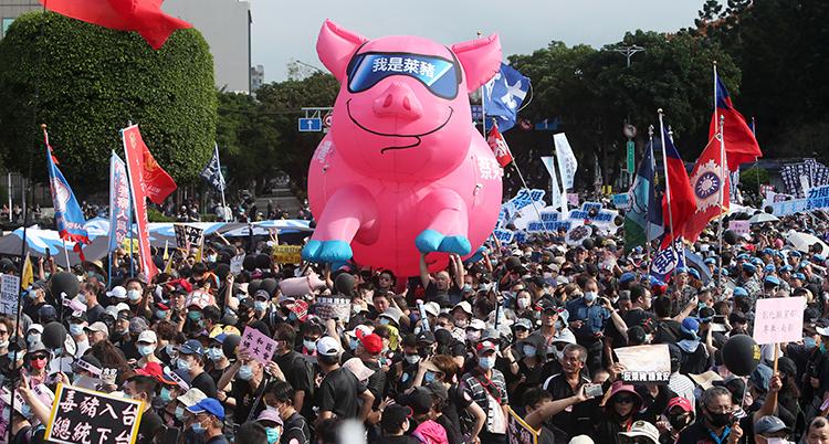 Massor av människor har samlats. De har blåst upp en ballong som ser ut som en gris.