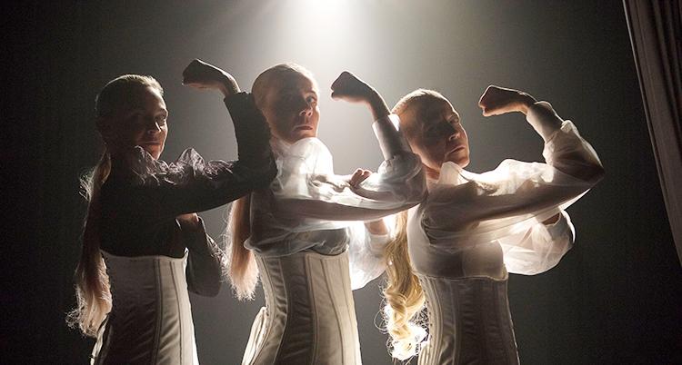 De tre kvinnorna står med varsin arm i luften. De har vita kläder på sig. De står på en scen. En lampa lyser på dem.