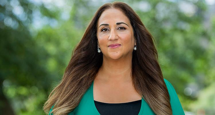 En kvinna med långt mörkt hår och grön tröja tittar in i kameran