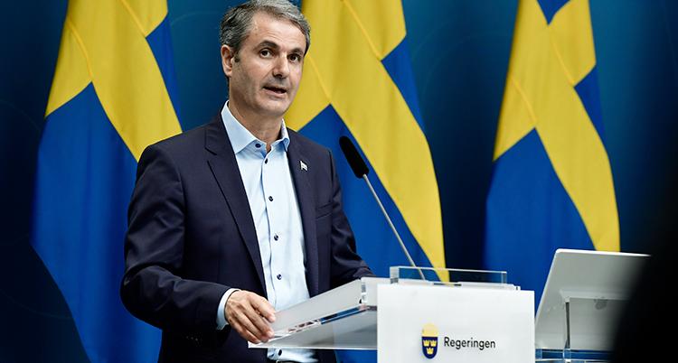 En man i grå kavaj och ljus skjorta står i en talarstol märkt med regeringen. Bakom syns tre svenska flaggor.
