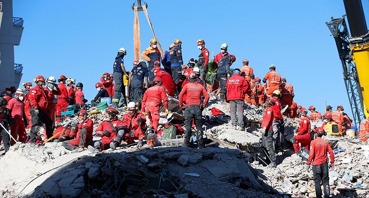 En massa människor i röda kläder står på en hög med sten och grus. Det som har varit ett hus.