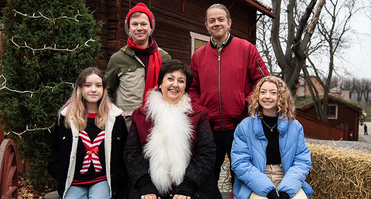 Ett foto på hela gruppen. De sitter och står utomhus. Bakom dem syns en julgran.