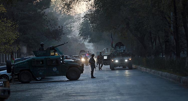 Militärklädda män med vapen syns vakta på en gata.