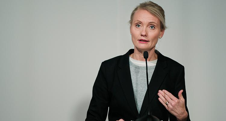 Hon talar i en mikrofon. Hon har svart kavaj på sig. Hon ser allvarlig ut.
