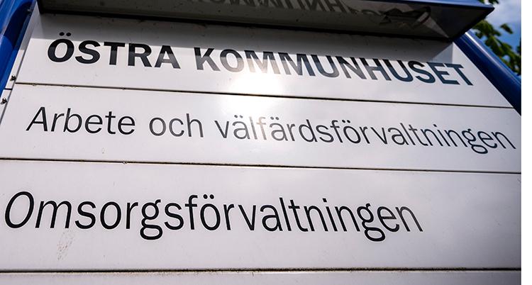 En vit skylt där det i svart står Östra kommunhuset, arbete och välfärdsförvaltningen, och omsorgsförvaltningen