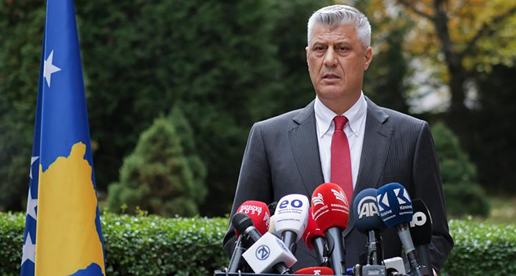 en man i grå kostym, vit skjorta och röd slips står vid ett podium utomhus och pratar i många mikrofoner från olika mediebolag