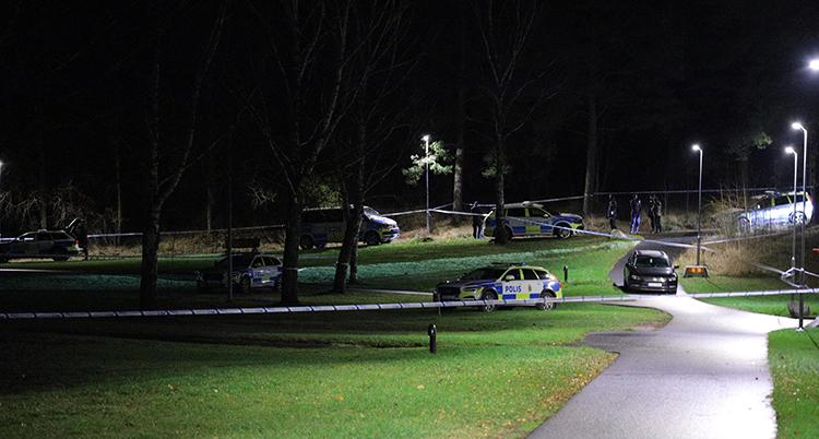 En stor gräsmatta är avspärrad med polistejp. Flera polisbilar syns.