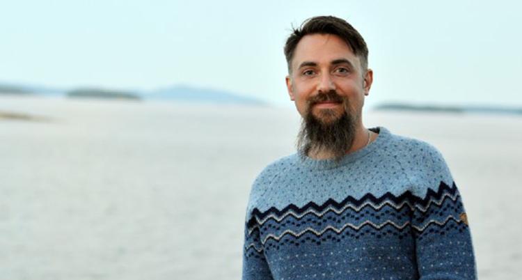 En man med mörkt hår och skägg och en mönsterstickad tröja står på en strand