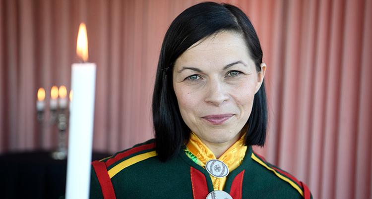 Närbild på Labba. Hon är klädd i en samiska dräkt i gult, grönt. rött och gult. Bredvid henne får ett levande ljus.
