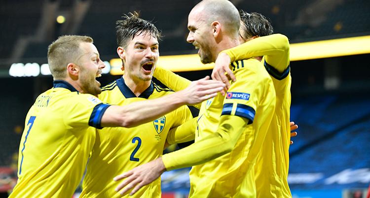 Fyra fotbollsspelare i gula landslagströjor klappar om varandra och jublar