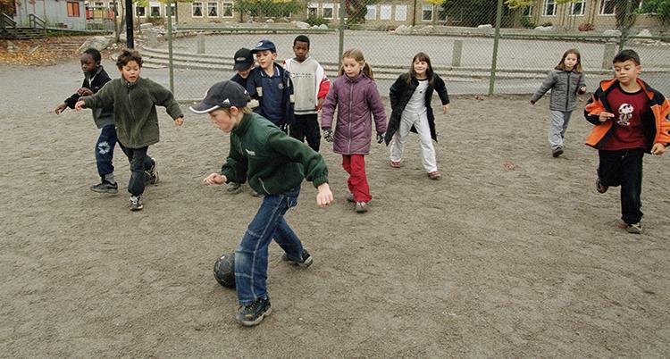 Barn spelar fotboll på en grusplan på en skolgård. Det var kar kyligt. De har vanliga kläder och jackor på sig.